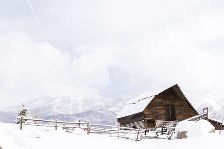 Aged barn on snowy hillside with ski lifts and ski slopes in background. Stock Photo - 17712967