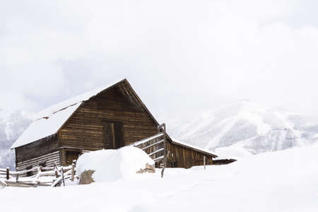 Aged barn on snowy hillside with ski lifts and ski slopes in background. Stock Photo - 17712964