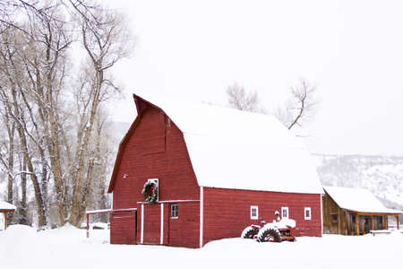 Red barn in snow on the farm in Colorado.