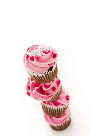 pastrie: Stack of pink cupcakes with engagement ring on top.