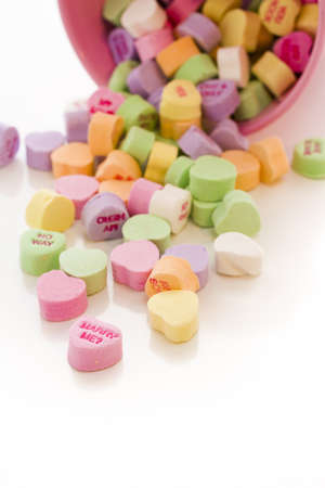 Conversation heart candies spilled from pink bucket.