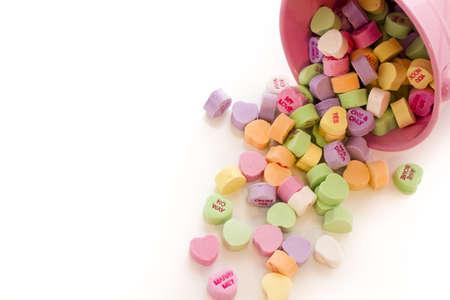 Conversation heart candies spilled from pink bucket.
