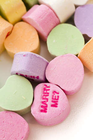 Pile of conversation heart candies on white background.