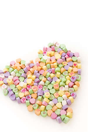 Pile of conversation heart candies in heart shape.