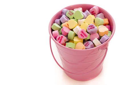 Conversation heart candies in pink bucket. Imagens