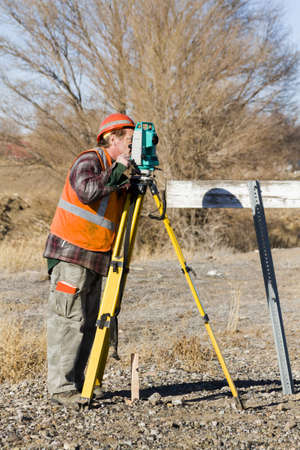 surveyors: Land surveyors measuring existing railroad bridge in rural area.