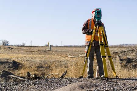 geodesist: Land surveyors measuring existing railroad bridge in rural area.