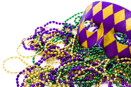 Mardi Gras beads and colorful mask on white backgound. Imagens