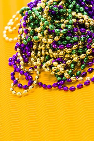 Mardi Gras beads yellow backgound. Stock Photo - 17874092