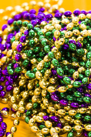Mardi Gras beads yellow backgound. Stock Photo - 17874133