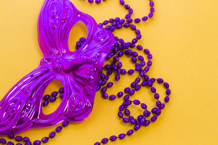 Mardi Gras beads and mask on yellow backgound.