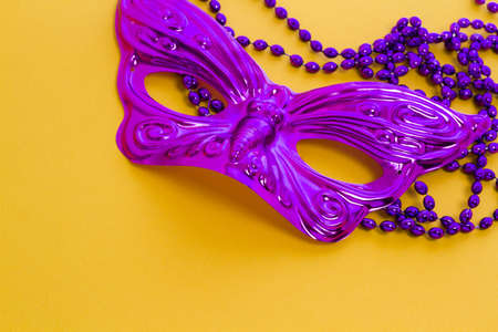 shrove tuesday: Mardi Gras beads and mask on yellow backgound.