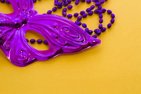 Mardi Gras beads and mask on yellow backgound. Stock Photo - 17874259