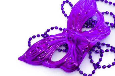 shrove tuesday: Mardi Gras purple beads and purple mask on white backgound.
