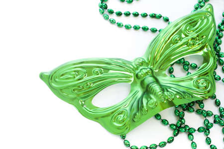 Mardi Gras green beads and mask on white backgound. Stock Photo
