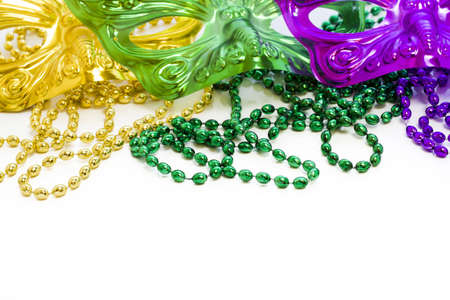 shrove: Mardi Gras beads and colorful masks on white backgound. Stock Photo