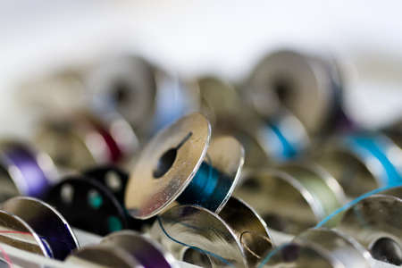 nad made: Colorful bobbins of thread in bobbin box in tailor shop. Stock Photo