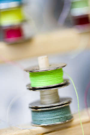nad made: Colorful bobbins of thread on bobbin stand in tailor shop. Stock Photo