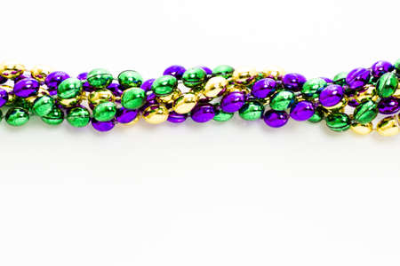 shrove: Multi color Mardi Gras beads on white background.