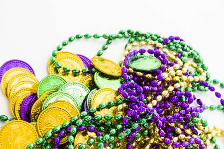 Multi color Mardi Gras beads and tokens on white background. Stock Photo - 17908465