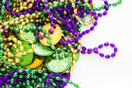 tokens: Multi color Mardi Gras beads and tokens on white background.