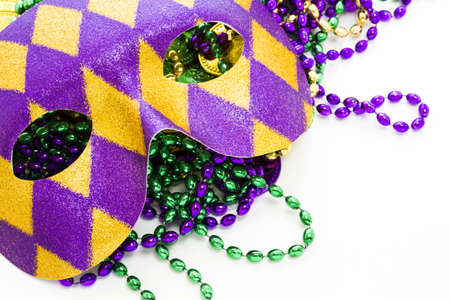 Multi color Mardi Gras beads, tokens and mask on white background. Stock Photo - 17908519
