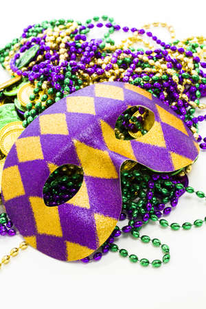 Multi color Mardi Gras beads, tokens and mask on white background.