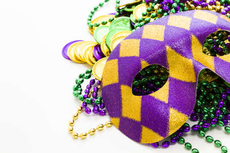 Multi color Mardi Gras beads, tokens and mask on white background. Stock Photo - 17908486