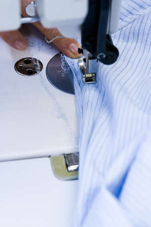 Hands work a sewing machine. photo