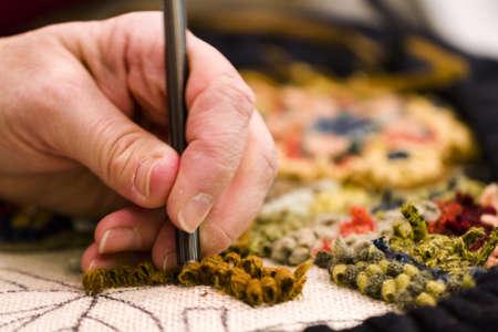 hooking: Hands work a hook in hug hooking craft.
