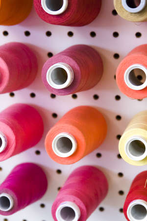 nad made: Colorful spools of thread on the wall in tailor shop.