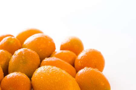 rutaceae: Organic kumquats on a white background. Stock Photo