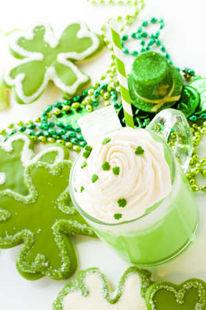 White chocolate shorrbread cookies in shape of four clover leaf with green hot chocolate. photo