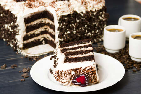Tiramisu cake, multiple layers of espresso infused chocolate cake, filled with chocolate mascarpone mousse and topped with whipped cream. photo