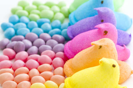 Rainbow color marshmallow peeps and jelly beans. photo