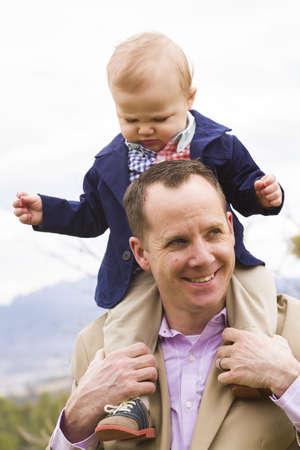 shoulder ride: Una familia joven con el beb� en el parque en un d�a de primavera agradable.
