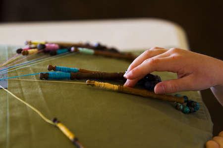 bobbin: Little girl learning old bobbin lace craft.