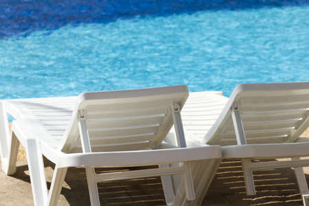 white plastic pool chairs at the swimming pool. photo