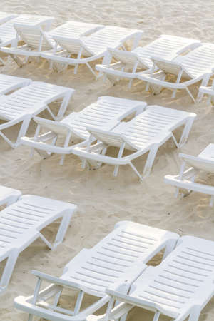 White pool chairs on the beach. photo