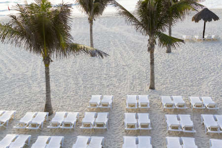 White pool chairs on the beach.