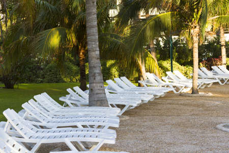 White pool chairs near the swimming pool at vacation resort in Mexico. photo