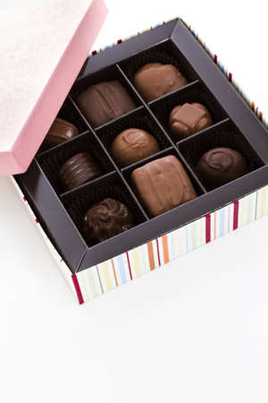 Box of assorted gourmet truffles on a white background.