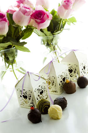Square white decorative lace heart favor boxes filled with gourmet truffles.