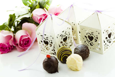 favor: Square white decorative lace heart favor boxes filled with gourmet truffles.