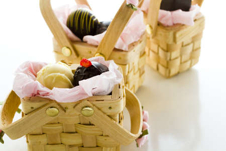 Miniature picnic baskets favor boxes filled with truffles. photo