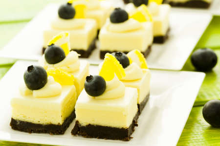 Small white chocolate cheesecake squares at dessert bar.