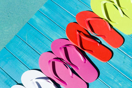 Colorful flip flops by a swimming pool. photo