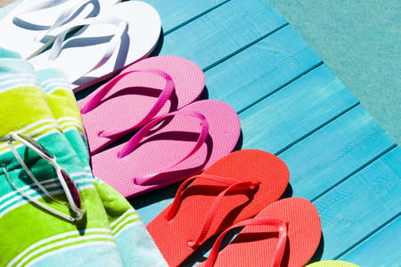 Colorful flip flops by a swimming pool.