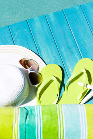 flipflops: Colorful flip flops by a swimming pool.