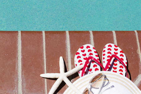 Colorful flip flops by a swimming pool. Stock Photo - 20488407